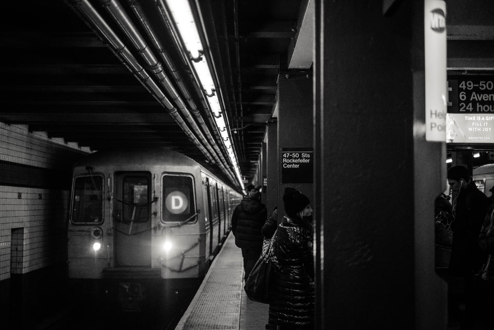 train passing in train station grayscale photography
