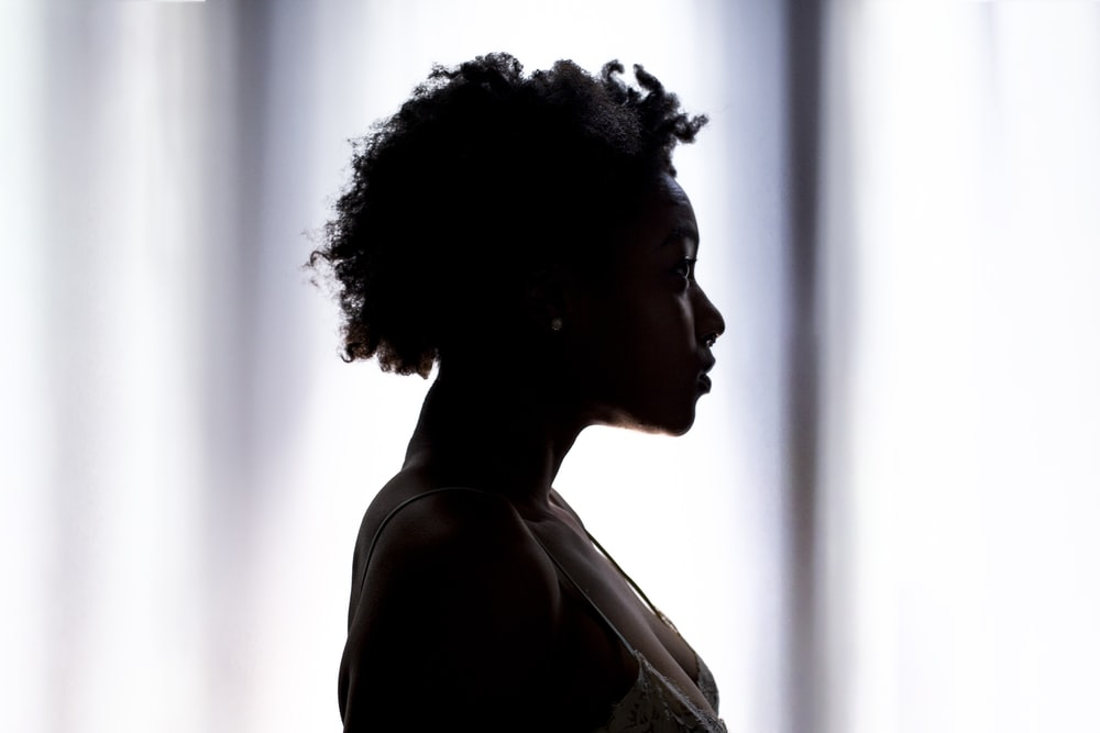 silhouette photo of woman standing near white cloth