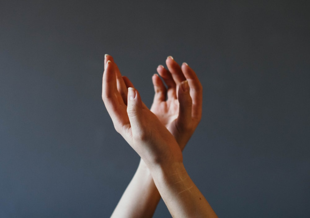 left hand over right hand with gray background