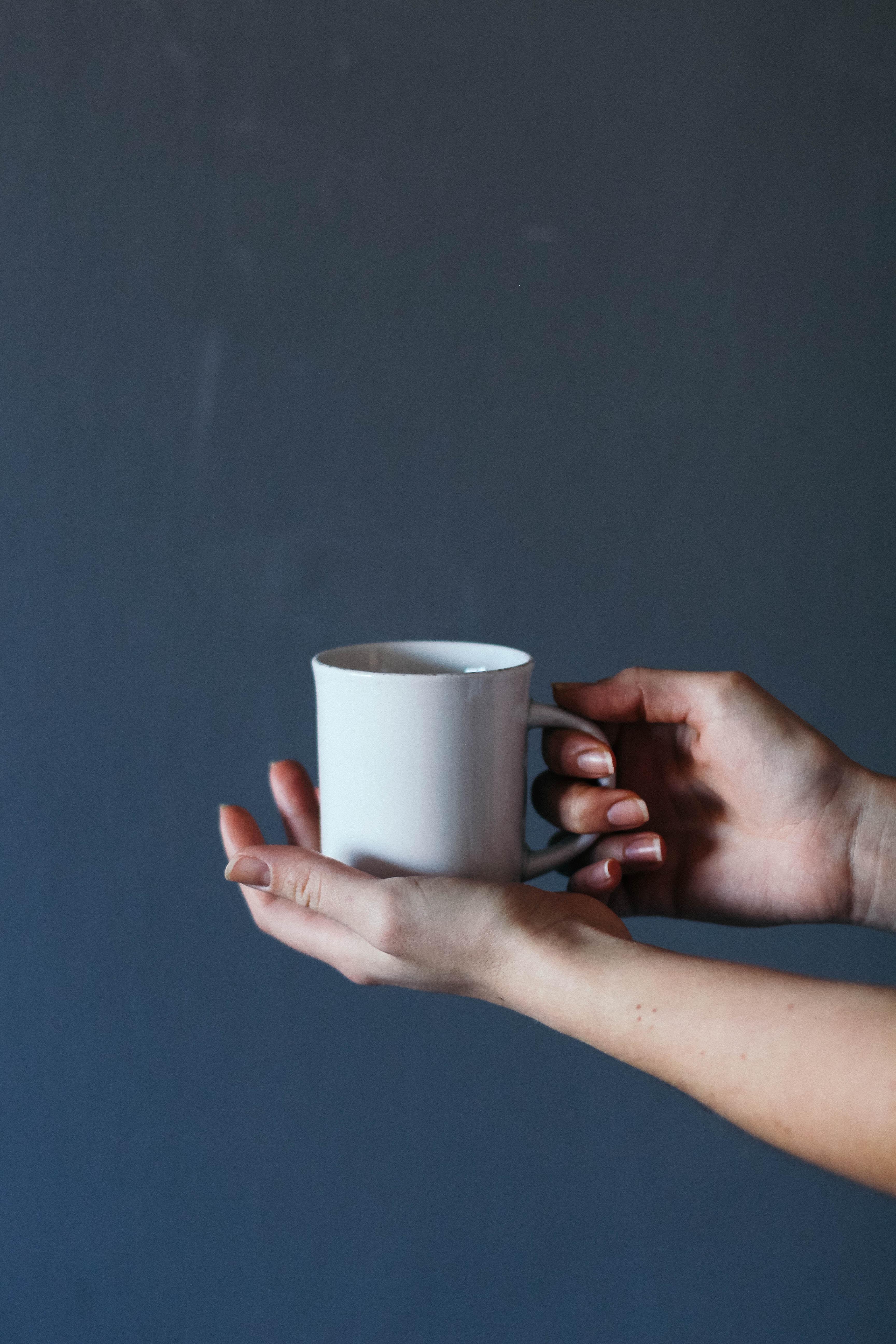 person holding grey ceramic mug