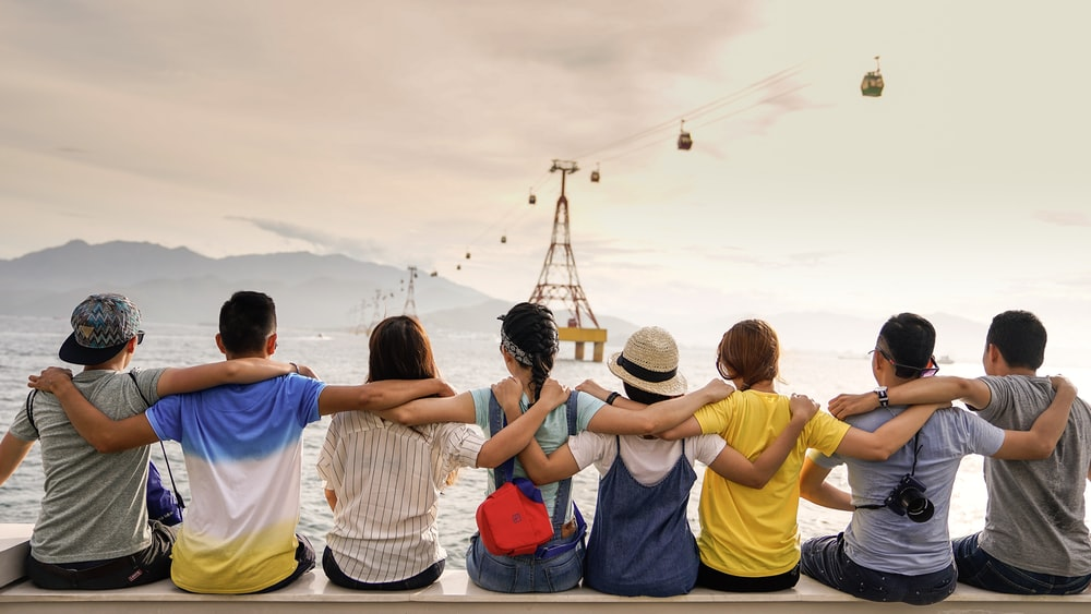 people holding shoulders sitting on wall