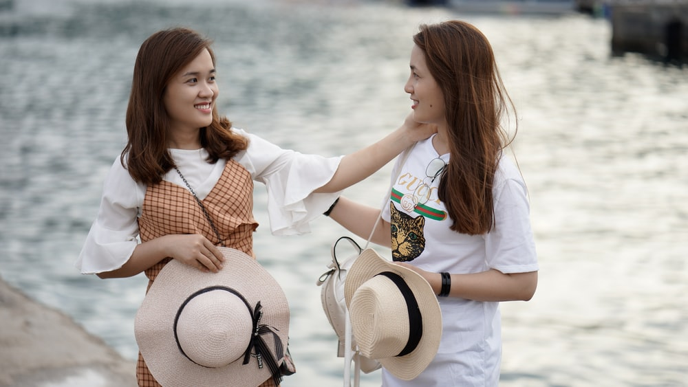 two women standing near body of water