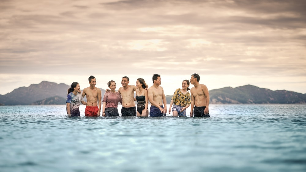 eight person standing in the middle of the sea
