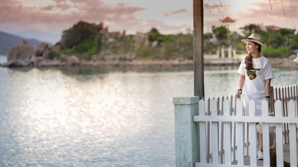 woman standing on dock near body of water