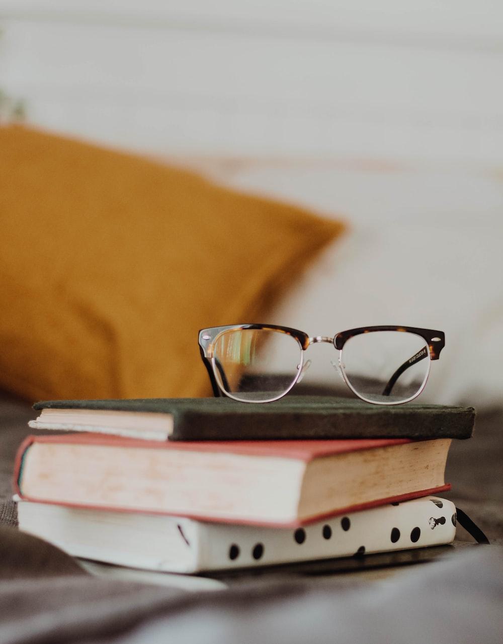 club master eyeglasses on pile of three books
