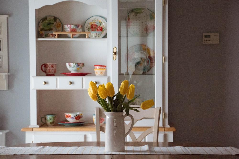 yellow tulip flowers in white ceramic vase