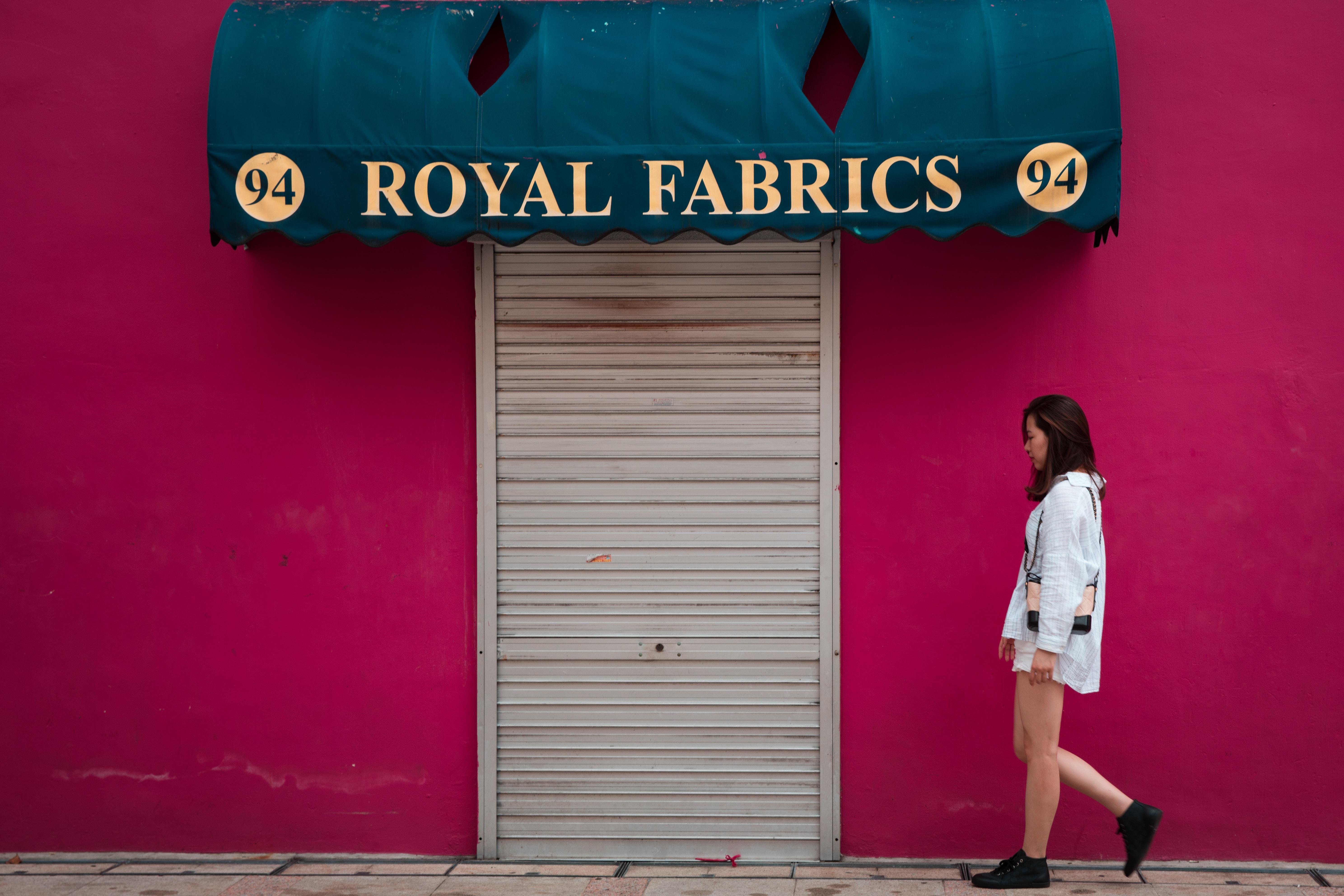 woman standing near Royal Fabrics signage