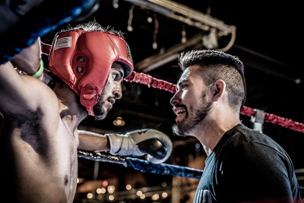 man in black talking to boxer inside ring