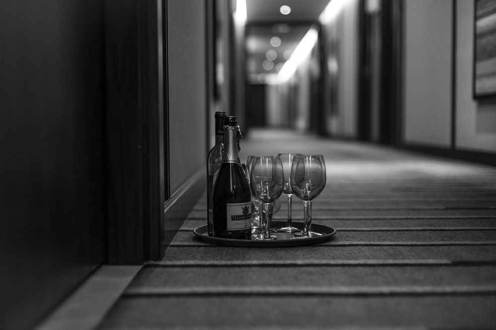 grayscale photo of wine glasses and bottle in tray