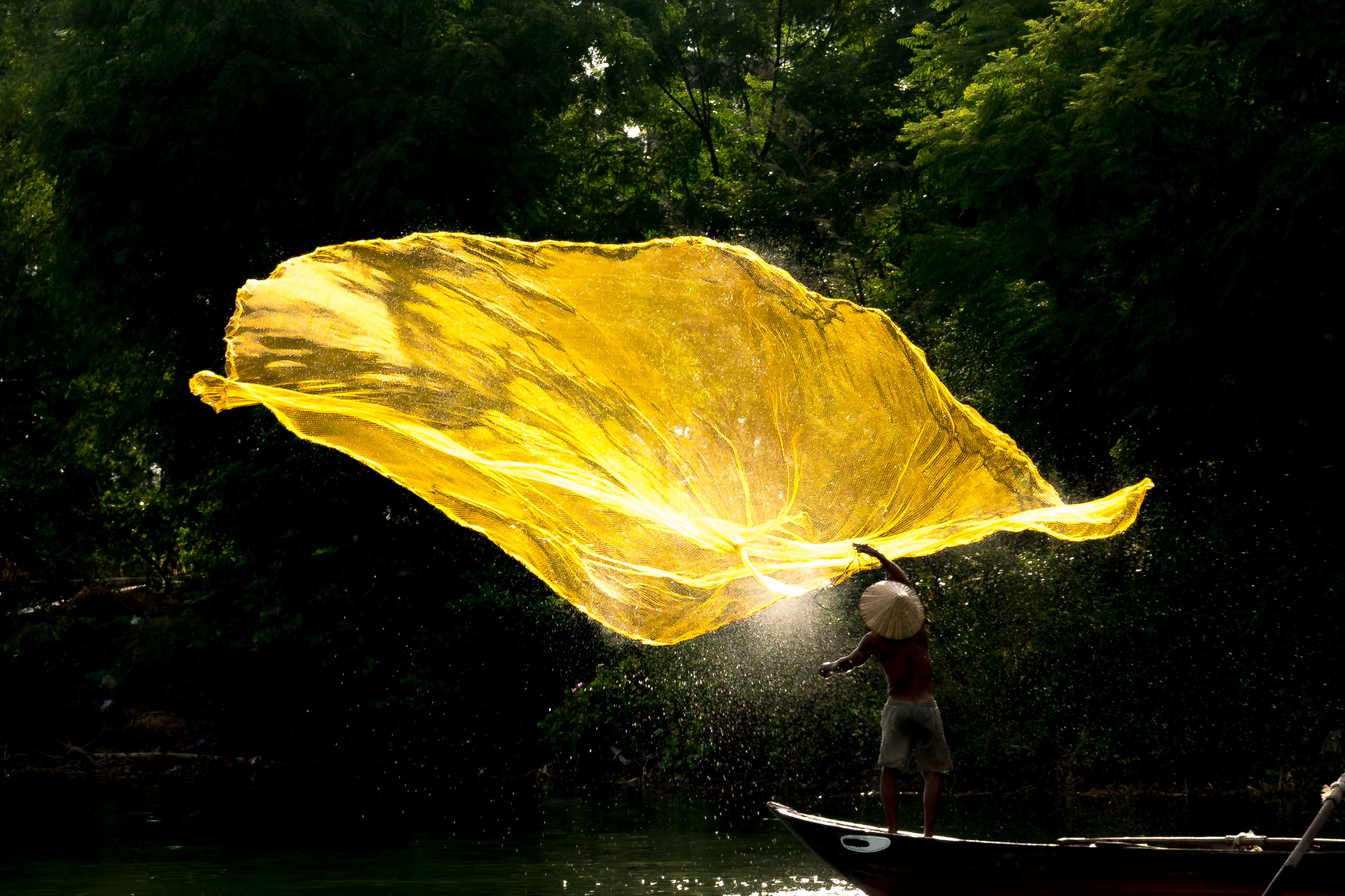 person throwing yellow fishing net above body of water at daytime