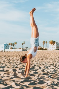 woman handstand on beach at daytime