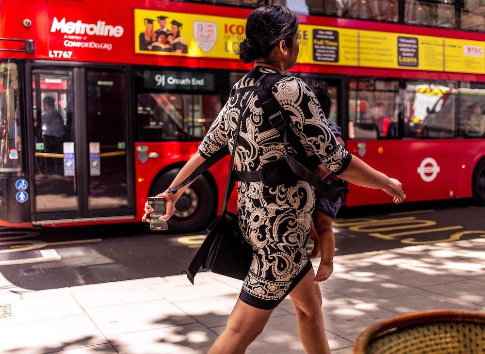 woman walking on street beside red bus