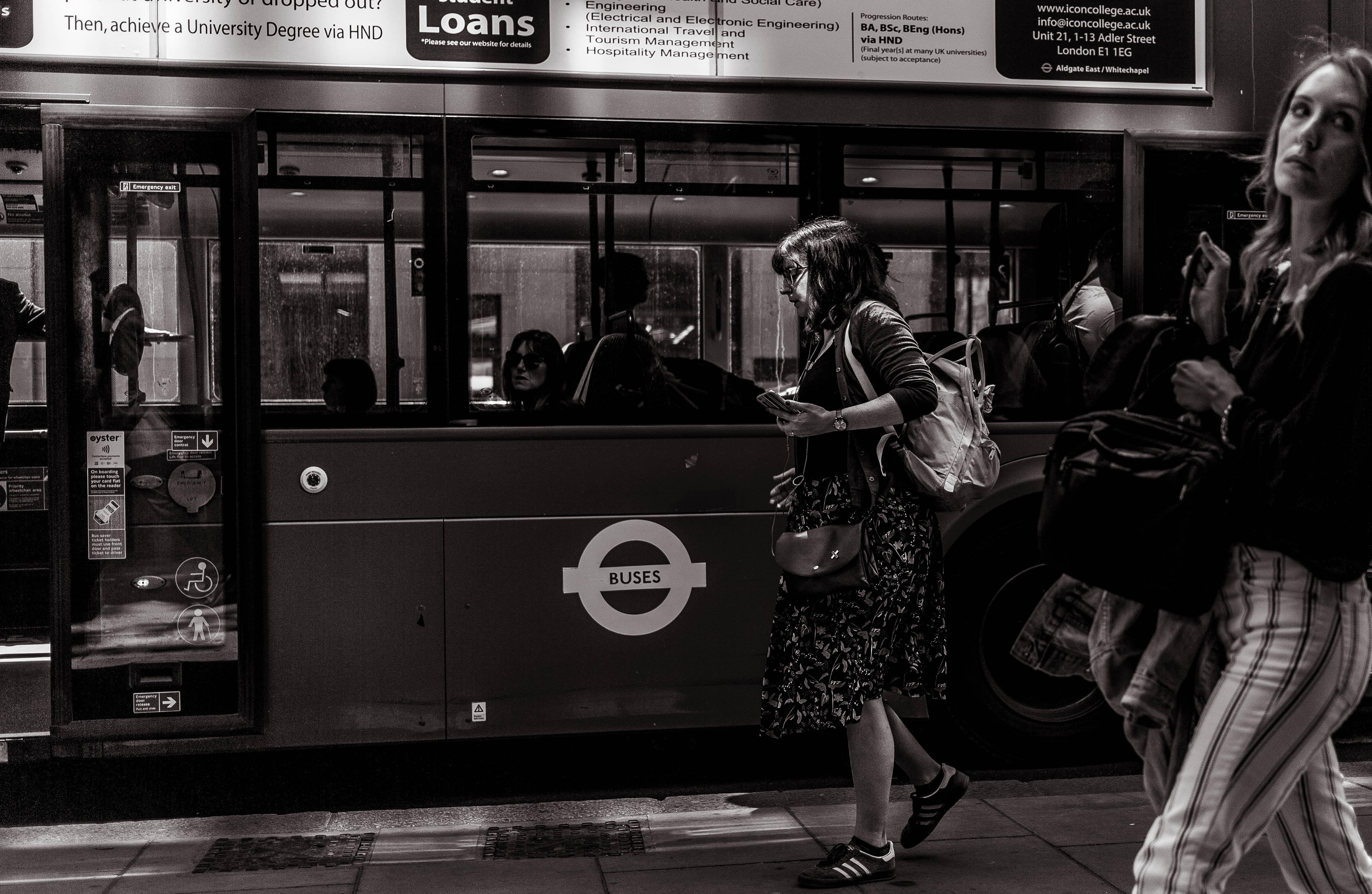grayscale photography of woman walking beside train