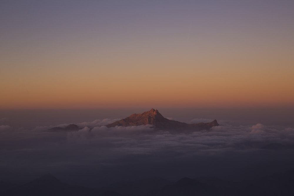 mountain covered by clouds during sunset