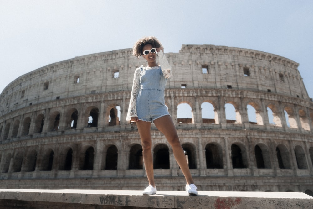 woman in blue romper shorts standing near The Coliseum