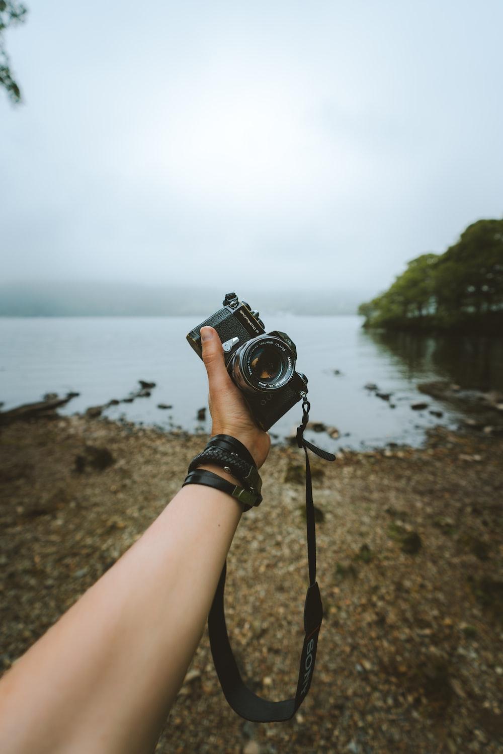 person holding black DSLR camera on seashore