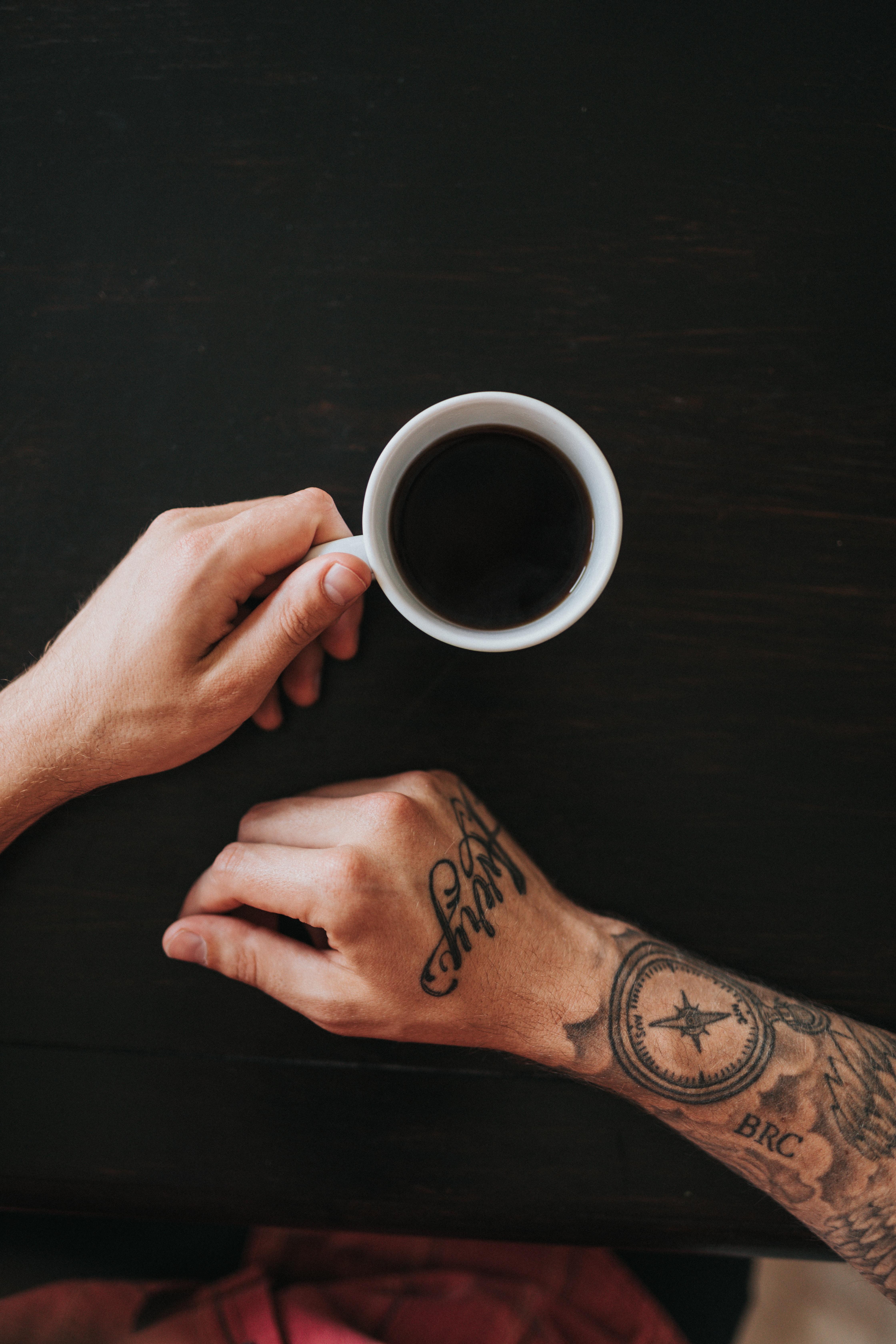 person holding white mug