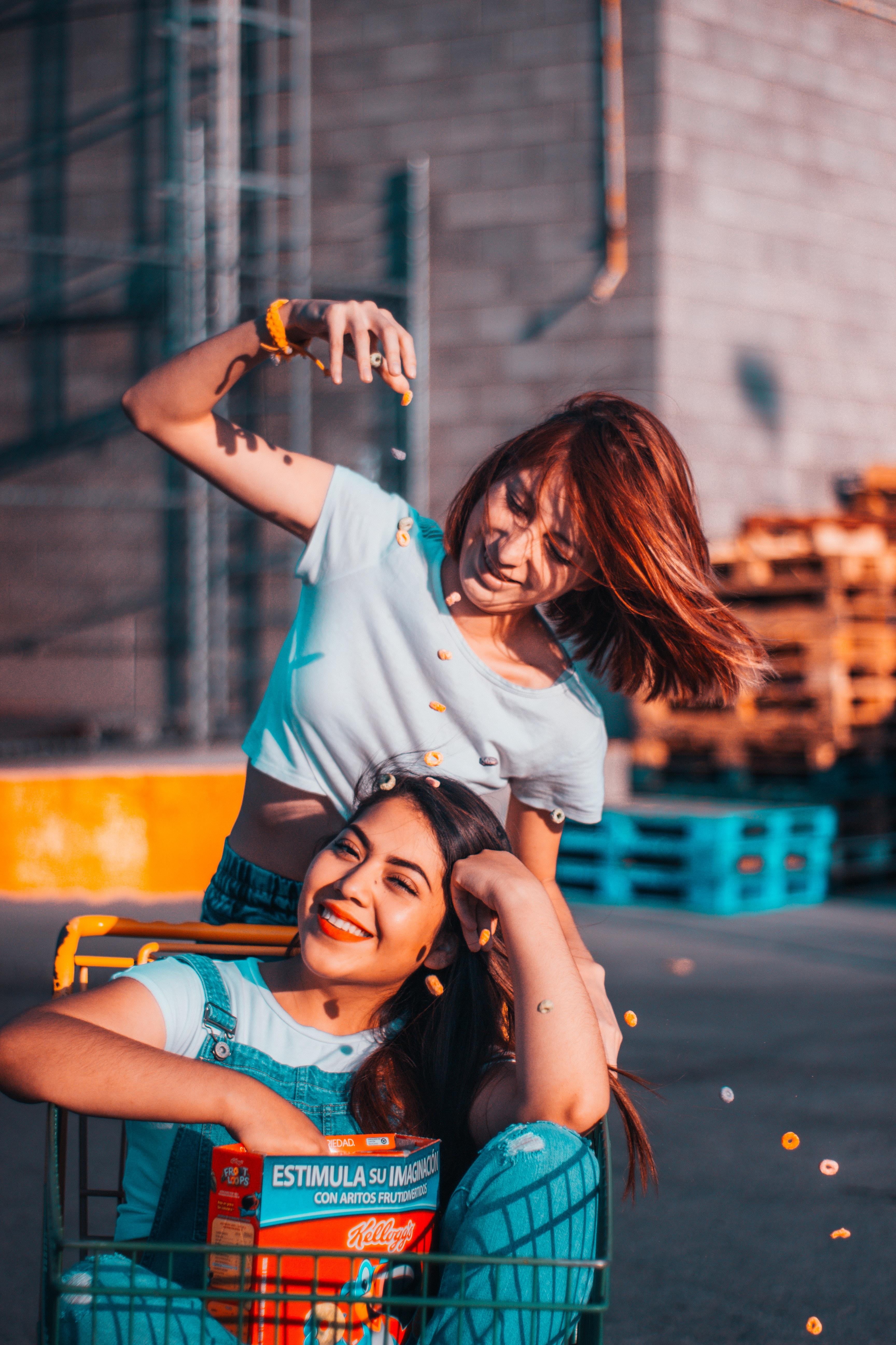 two women riding push cart