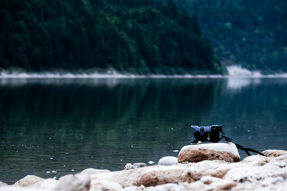 black DSLR camera near body of water