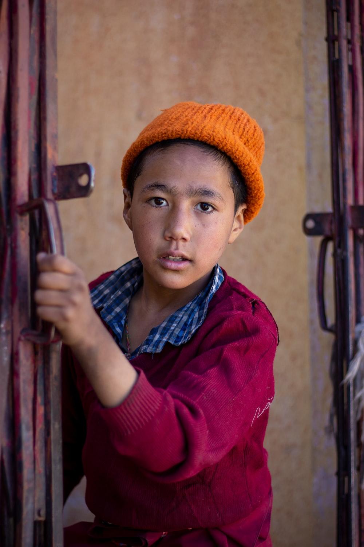 boy holding metal gate