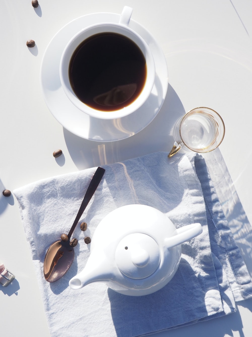white ceramic teacup filled with coffee on white ceramic saucer beside ceramic teapot