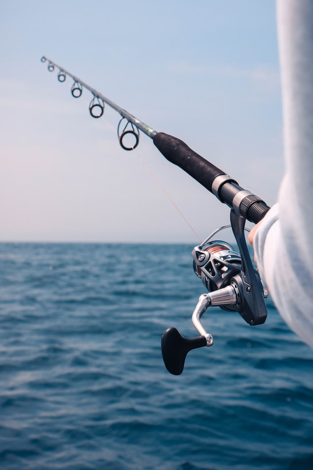 fishing pole with reel in hand with view of open water