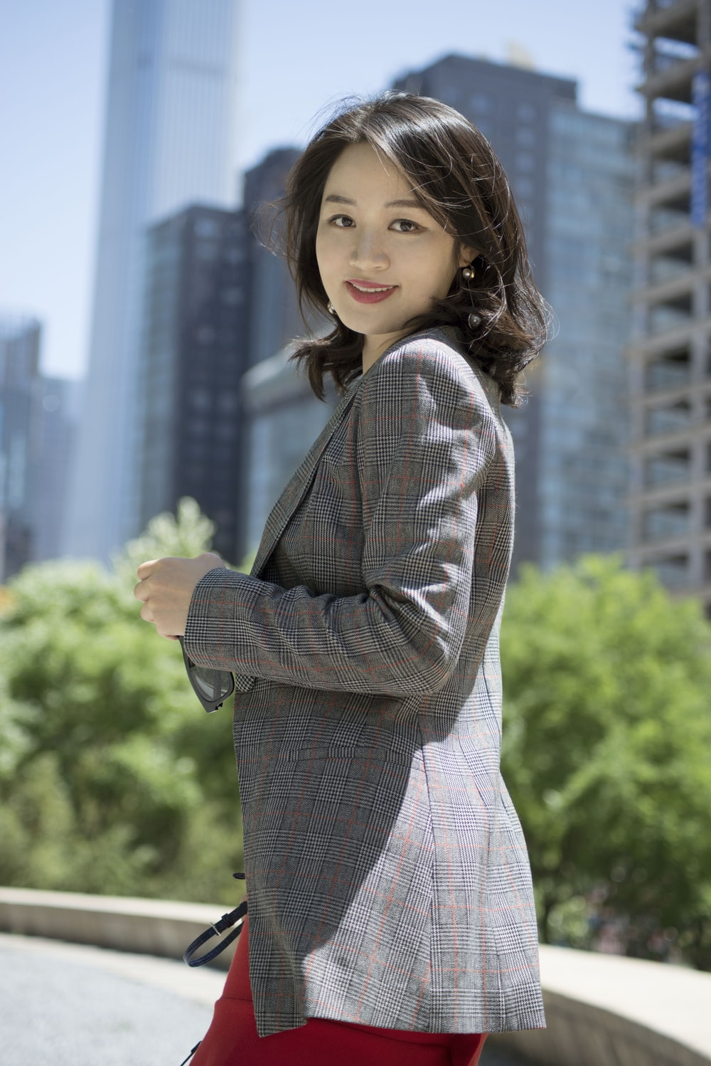 smiling woman wearing red, black, and gray plaid blazer
