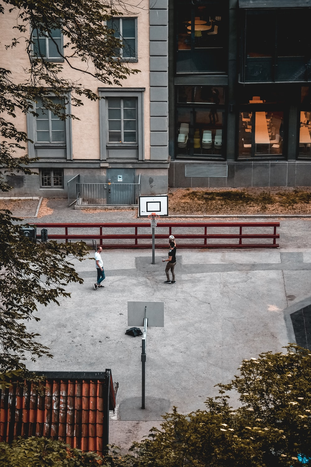 two men playing basketball on basketball court near buildings
