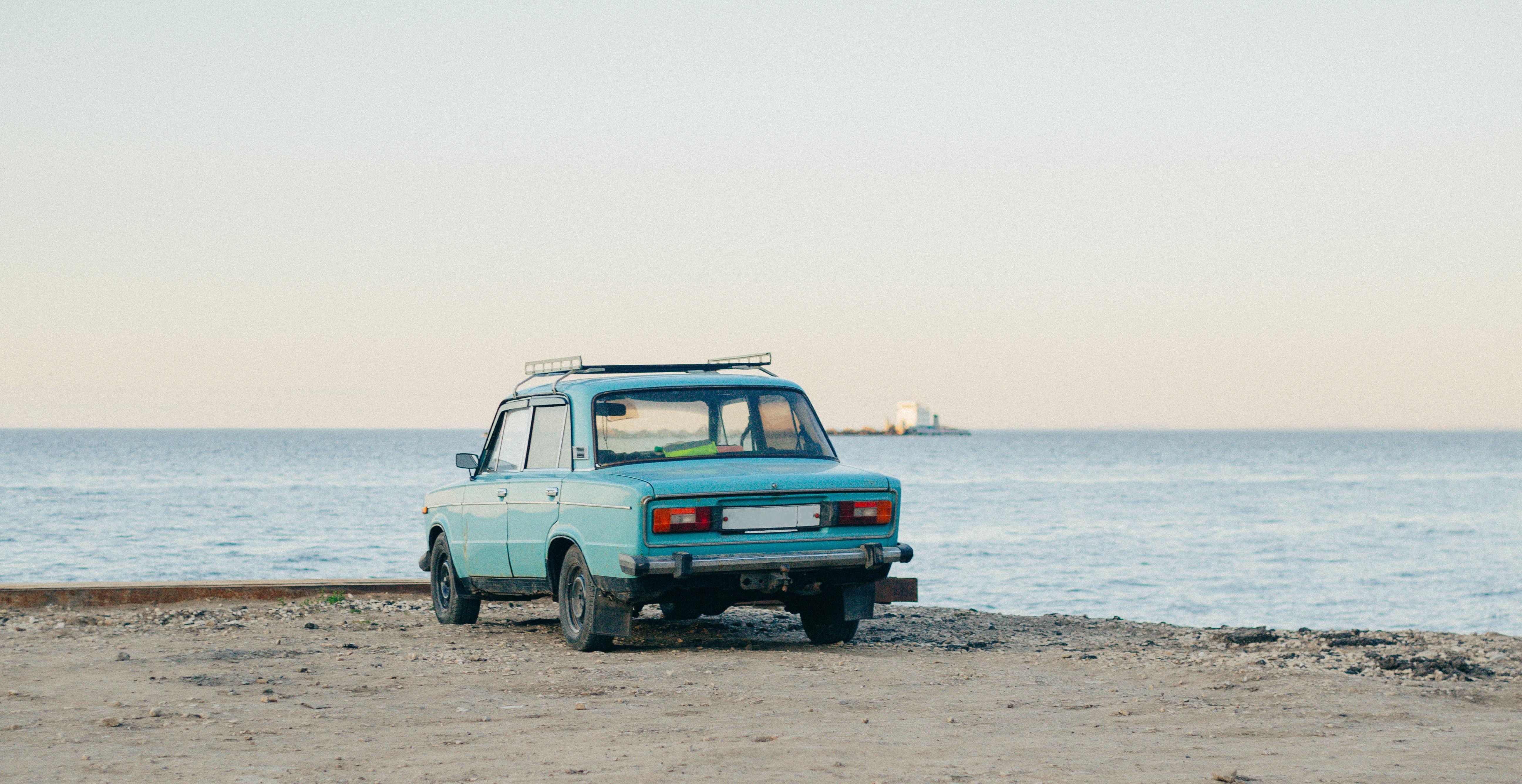 blue sedan near body of water