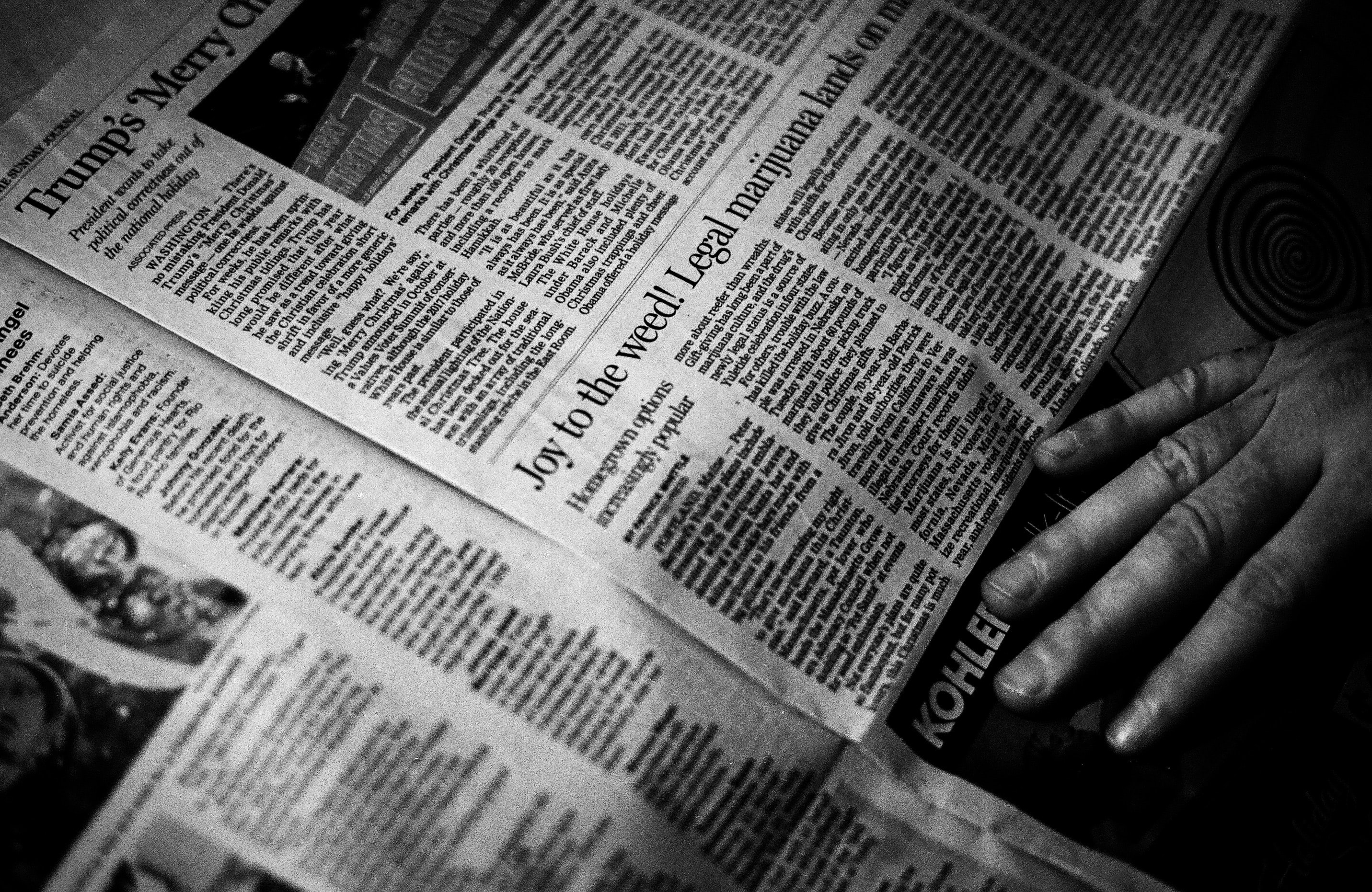 person's right hand near newspaper
