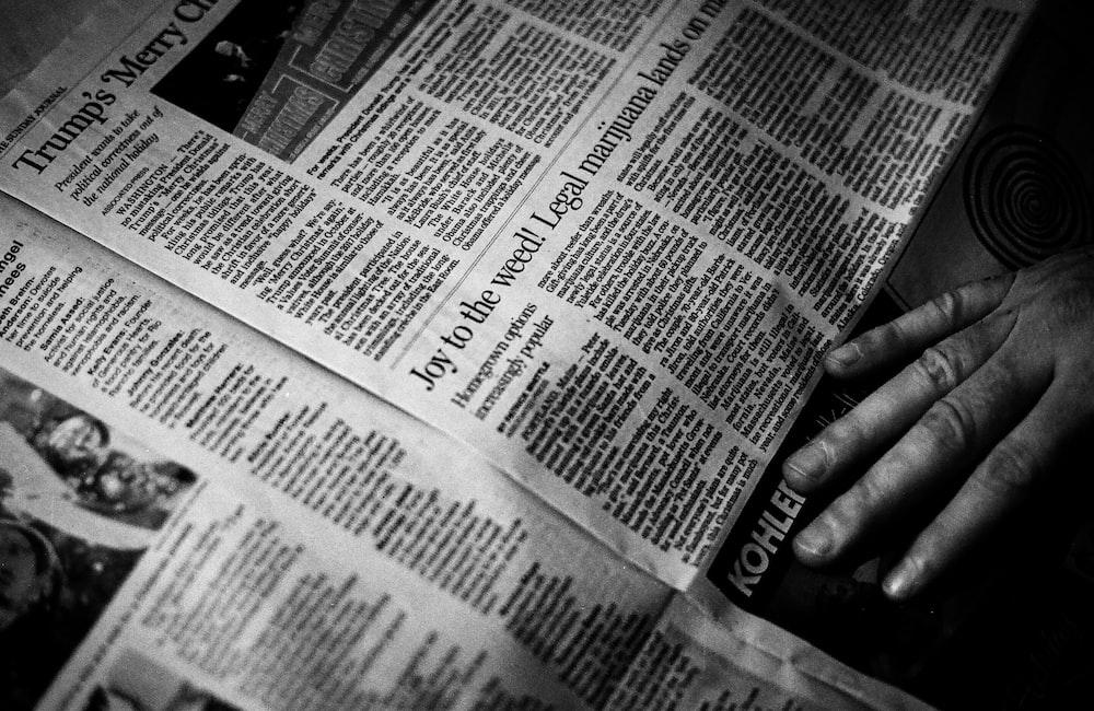person's right hand near newspaper