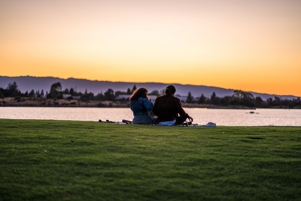 man and woman sitting on grass while fronting body of water