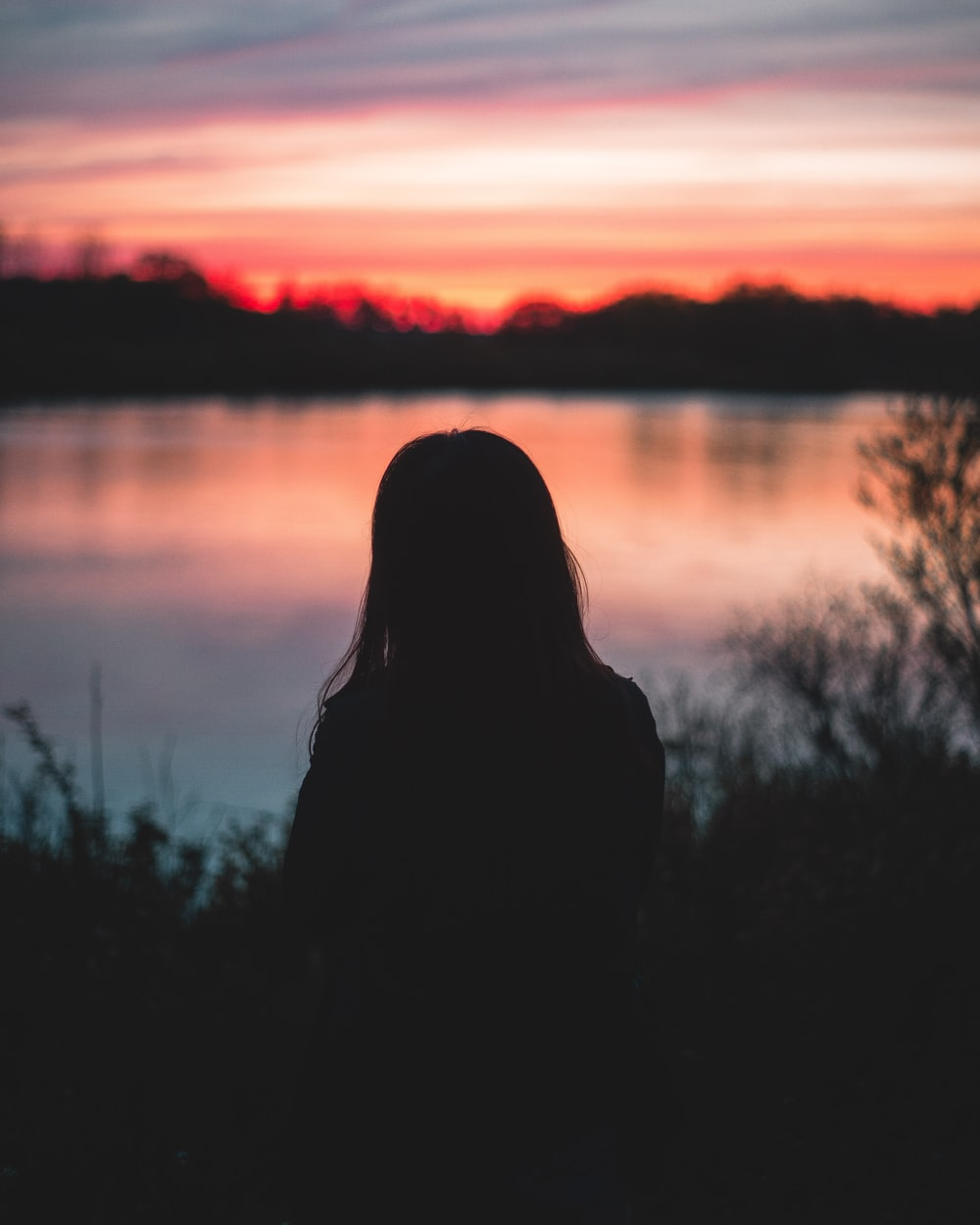 woman facing on body of water during sunset