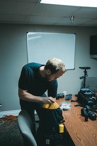 man holding blue and black bag near camera on desk