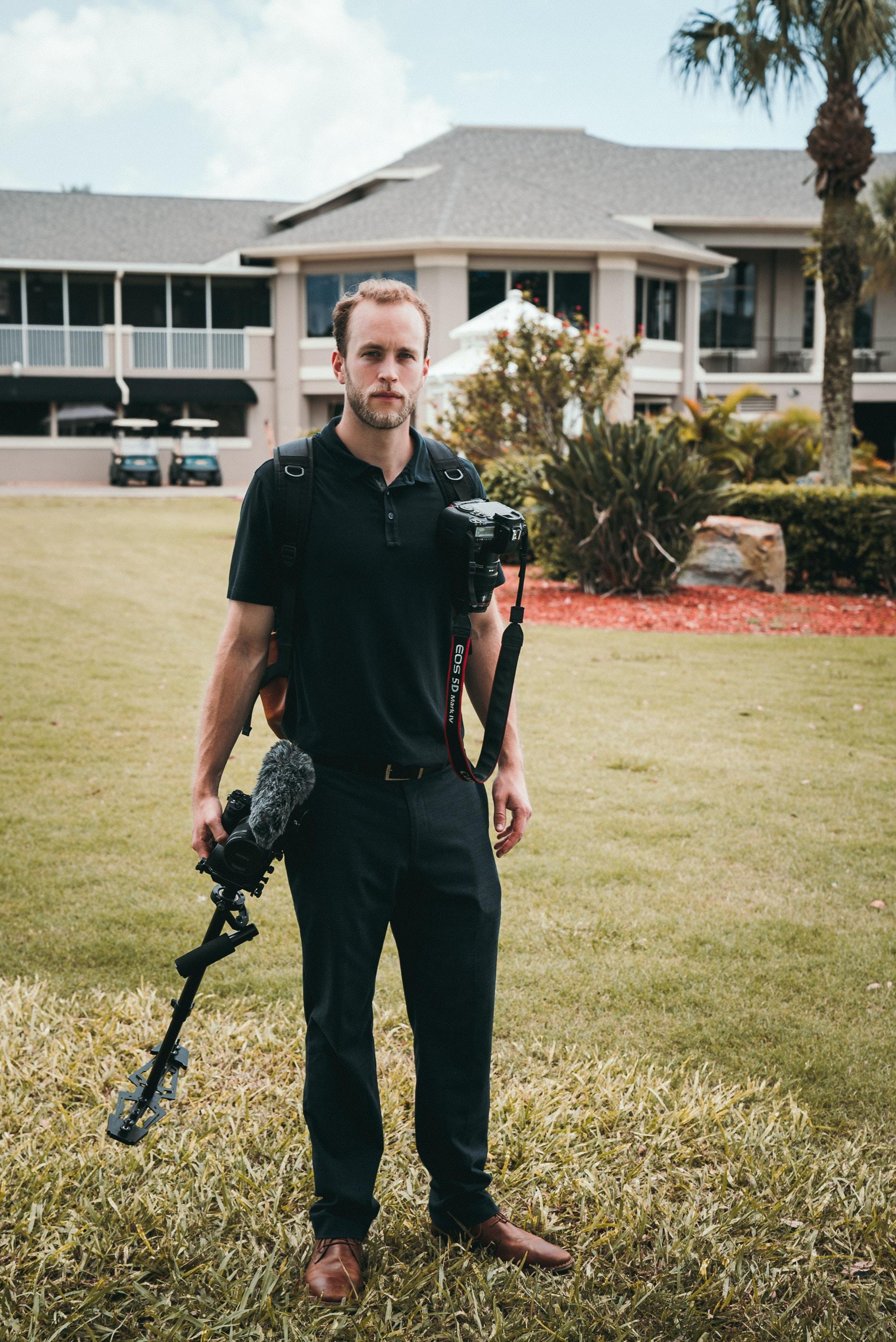 man holding black glide cam and black Canon DSLR camera