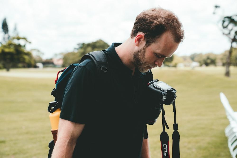 man in black t-shirt looking at his camera