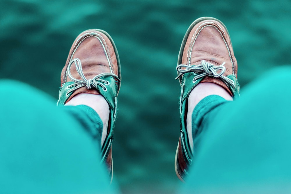 person wearing brown boat shoes