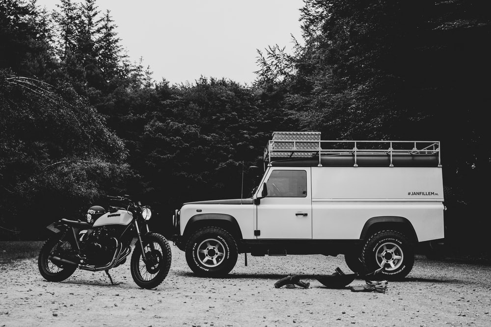 grayscale photography of motorcycle and car between trees