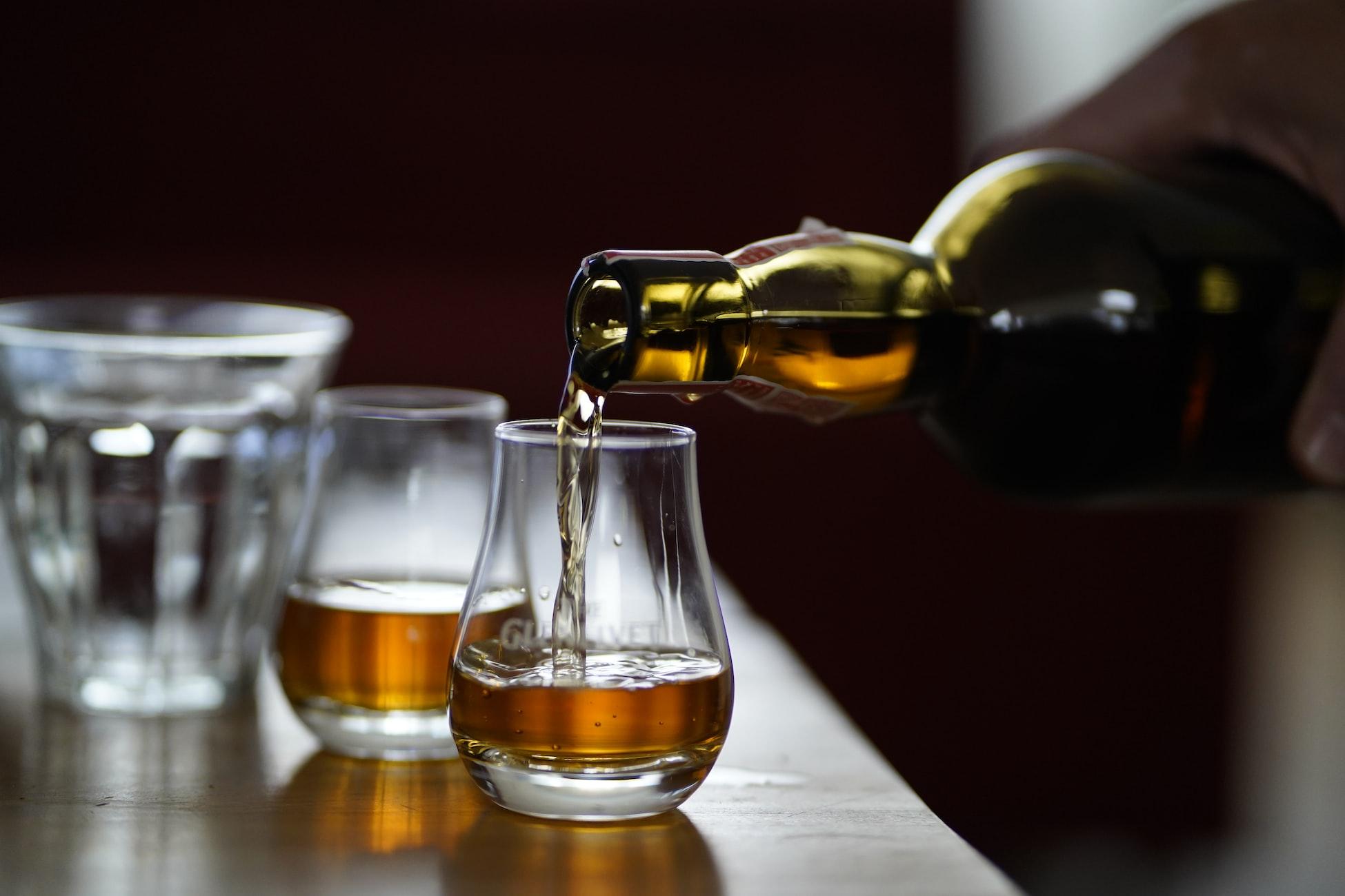 Nalievanie whisky z fľaše do pohárika