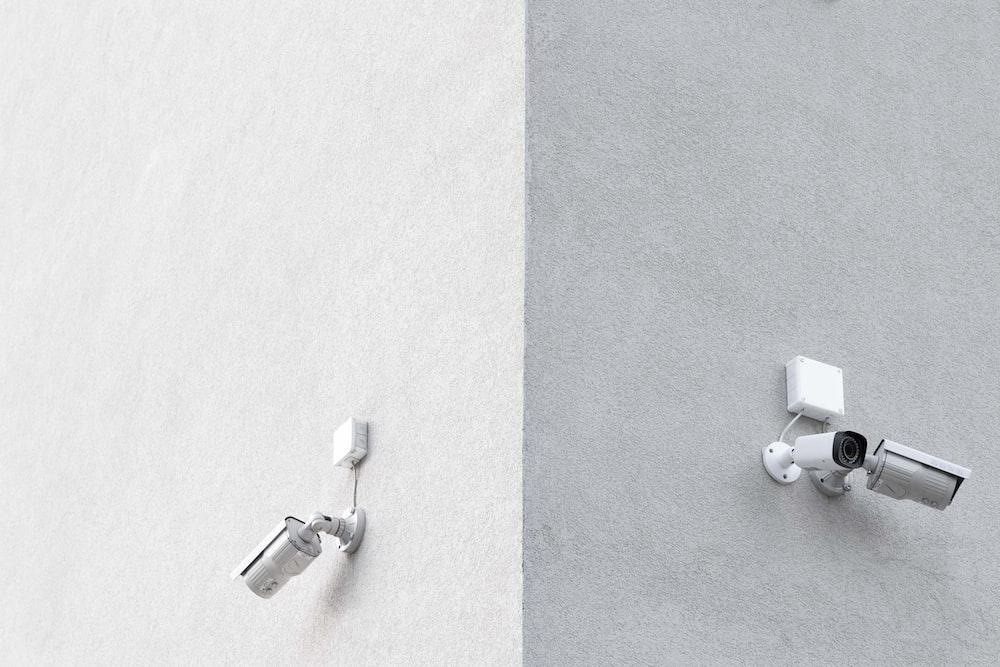 three white CCTV cameras mounted on wall