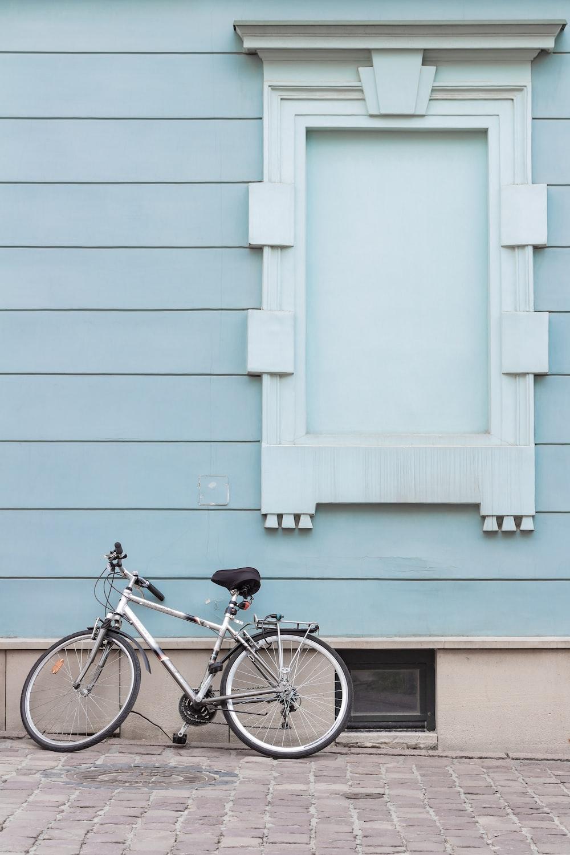 gray city bike parking on pavement on wall