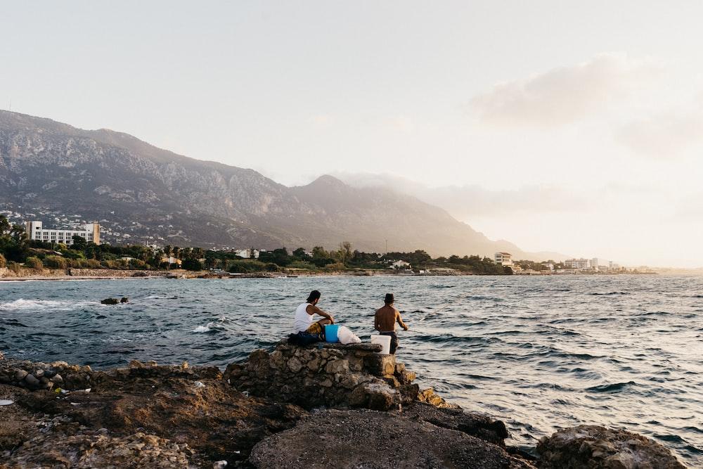 two men near sea at daytime