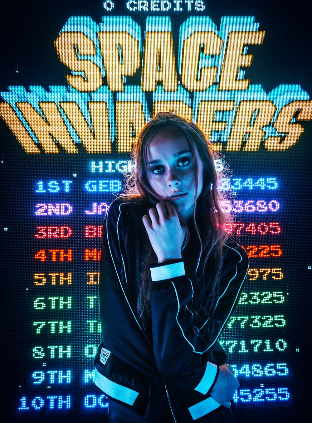 woman posing for photo in front of Space Invaders scoreboard