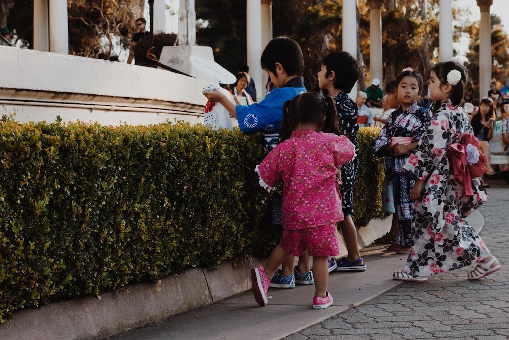 children wearing yukata standing near bush