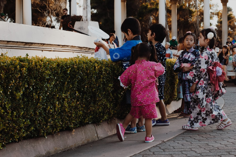children wearing yukata standing near bush