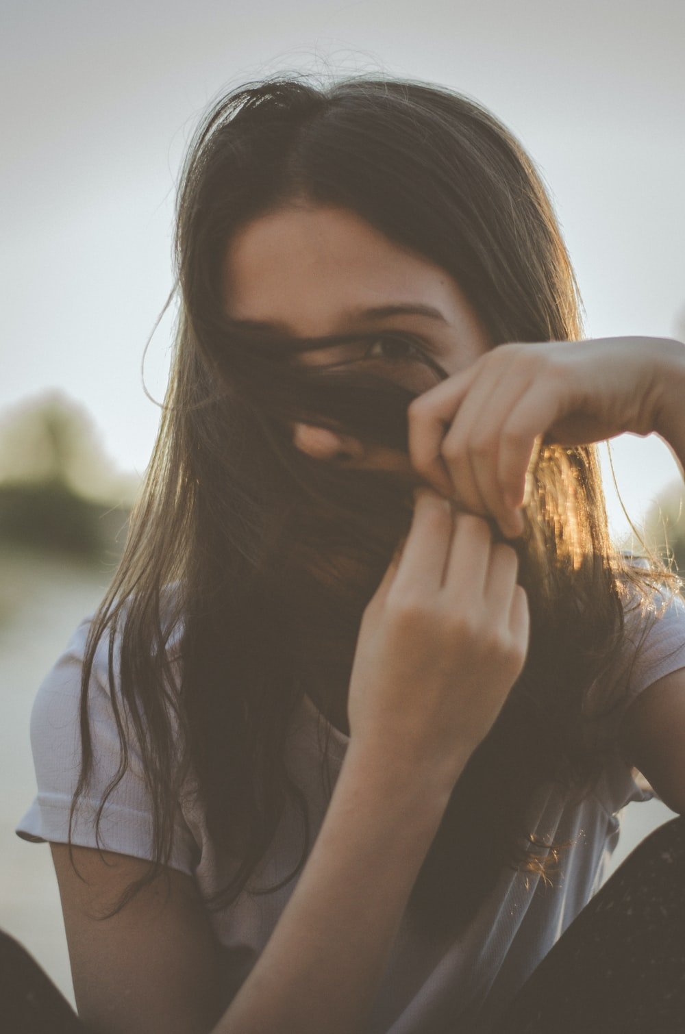 man covering her face with her hair