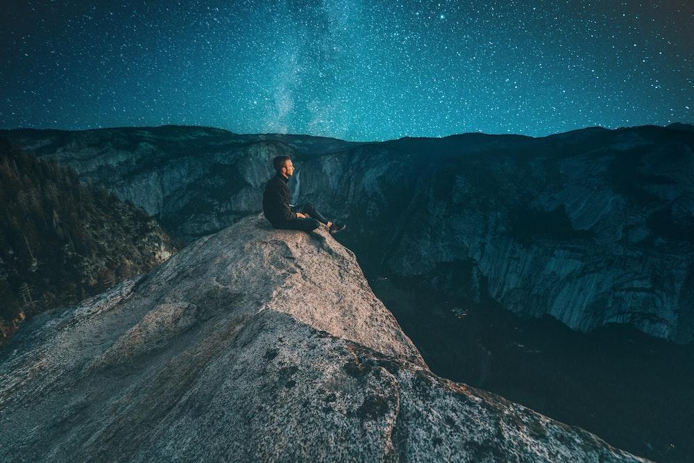 person sitting on mountain