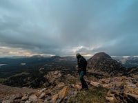 man standing on rocky mountain under gray cloudy sky