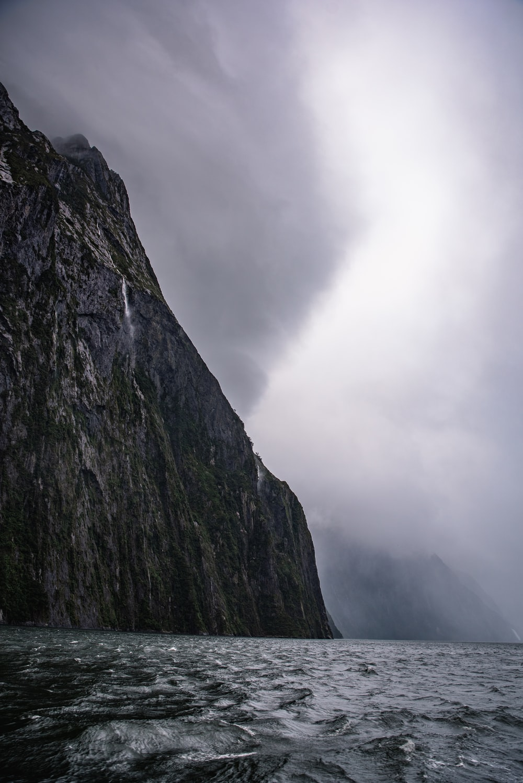 grey hill near body of water