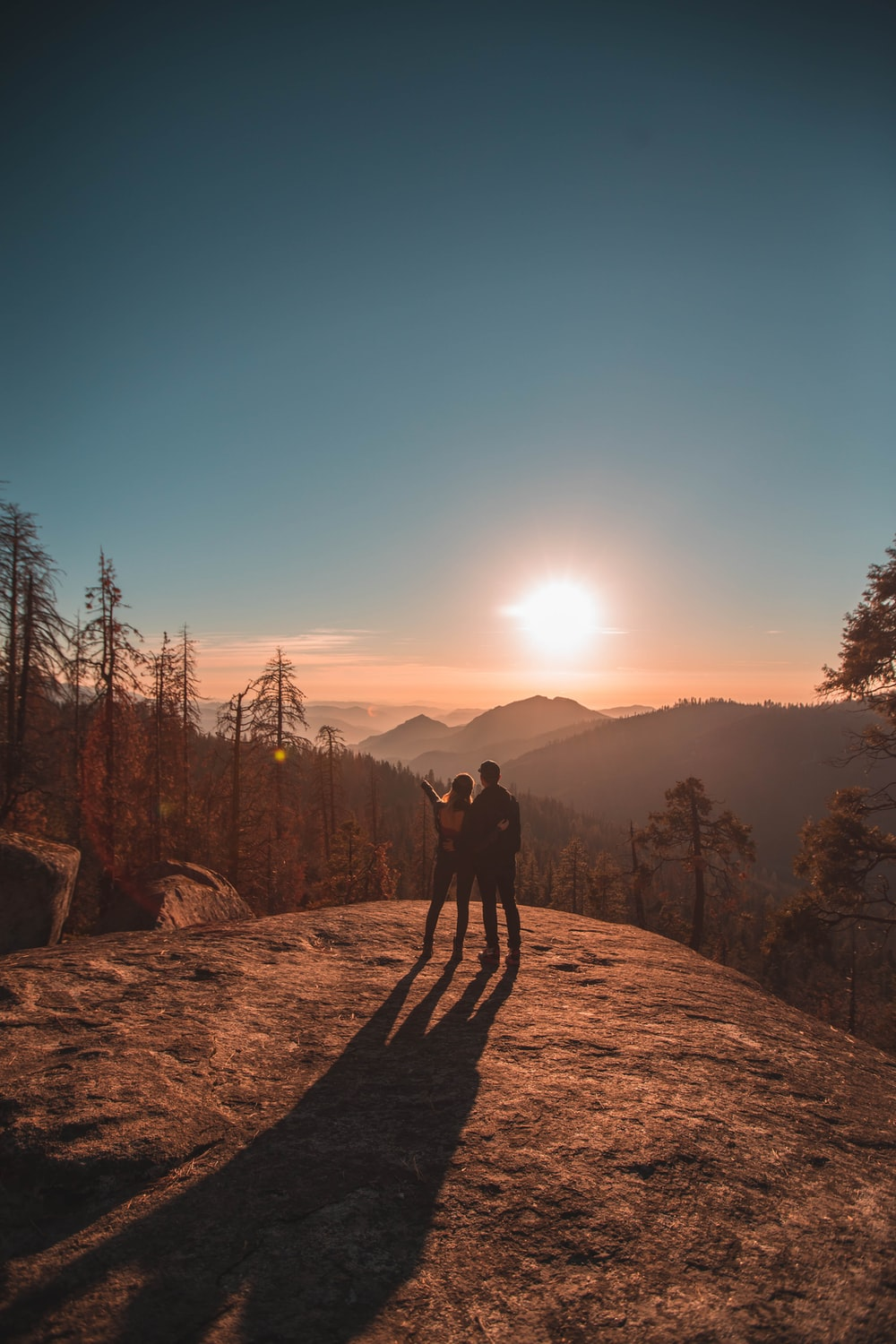 silhouette of man and woman on hill